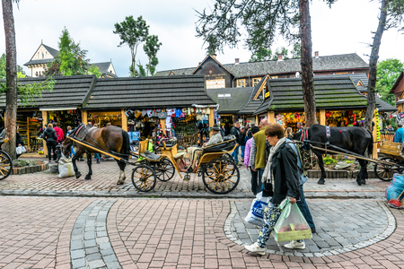 ZAKOPANE, POLAND - AUGUST 17, 2016: Main promenade in Zakopane, tourist on the street with shops, people enjoy local folclore in Poland, tourism in the summer