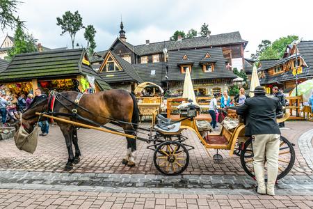 ZAKOPANE, POLAND - AUGUST 17, 2016: Touristic season in Zakopane, tourist attraction in city center on the Krupowki street. Carriage with coachman and harnessed horse