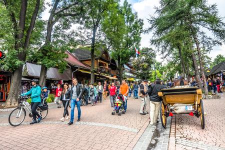 ZAKOPANE, POLAND - AUGUST 17, 2016: Touristic season in Zakopane, tourist recreation on the Krupowki street. Carriage with coachman and harnessed horse