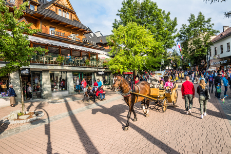 ZAKOPANE, POLAND - AUGUST 17, 2016: City center of Zakopane, People tourists enjoy carriage ride through Krupowki street in the summer season