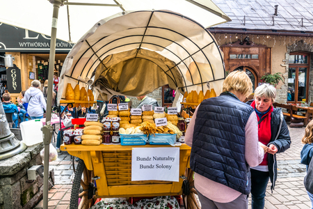 ZAKOPANE, POLAND - AUGUST 17, 2016: Street trading in the city center of Zakopane - people buying oscypek, traditional polish snack - street food and tourist attraction in the summer season Editorial
