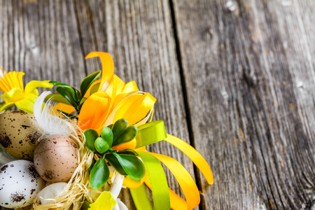 Easter background with easter eggs and spring flowers on wooden table
