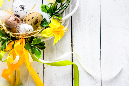Easter background, white planks with easter eggs and spring flowers, wreath on door