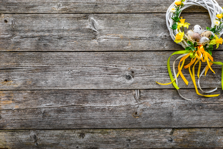 Easter background, rustic wood with easter eggs and spring flowers, wreath on door