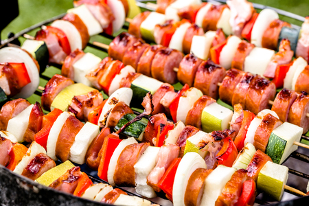 Grilling skewers with meat and vegetables on barbecue grill, outdoor bbq, grid with colorful grilled food, close-up