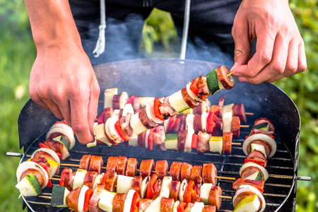 Summer grilling food, sausage, vegetables and kebab meat on barbecue grill over smoke and hot charcoal Stock Photo