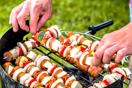 Grilling food on barbecue grill in the summer garden, cook's hands preparing skewers with vegetables and meat, outdoor party with bbq on grass Stock Photo
