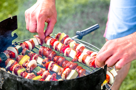 Vegetable meat kebabs and sausage grilled on barbecue grill, people grilling on grass, summer party concept Stock Photo