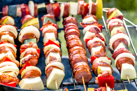 Grilling skewers with vegetables and sausage on barbecue grill, outdoor bbq, grid with colorful grilled food, close-up