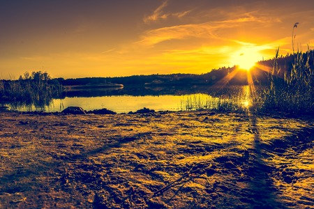 Summer landscape with sunset on the lake. Beautiful orange sundown or sunrise over forest and peaceful water with reflection of sun light, warm scenery in nature. Stock Photo