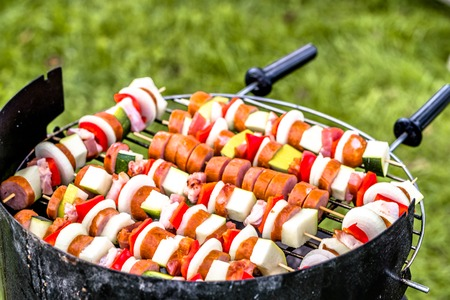 Grilling food on barbecue grill, skewers with vegetables and sausage, grilled food with outdoor bbq on grass Stock Photo