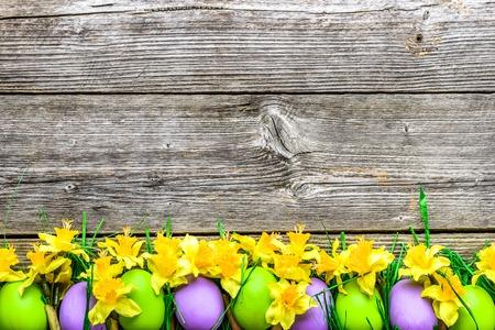 De lentepaaseieren, achtergrond met kleurrijke eieren en gele narcissen op houten lijst