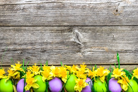 Spring easter eggs, background with colorful eggs and daffodils on wooden table