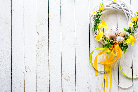 Easter background with spring easter eggs and flowers, wreath on door Stok Fotoğraf - 94484592