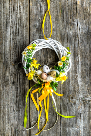 Easter background with spring easter eggs and flowers, wreath on door Stok Fotoğraf - 94484627