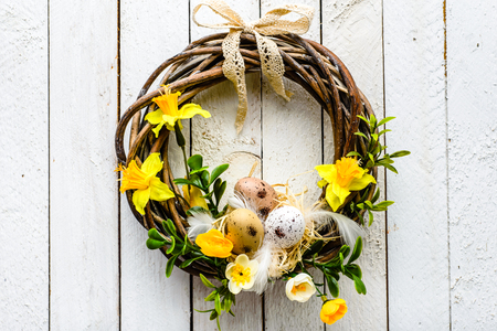 Easter background with spring easter eggs and flowers, wreath on door Stok Fotoğraf - 94484626