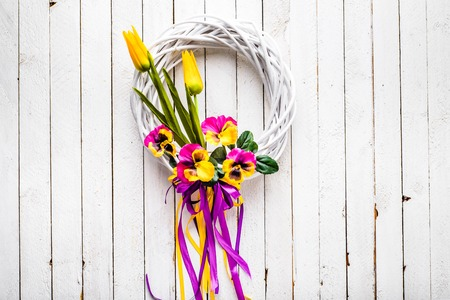 Easter background with spring flowers wreath on door
