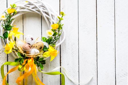 Pasen-achtergrond met de lentekroon het hangen op deur Stockfoto
