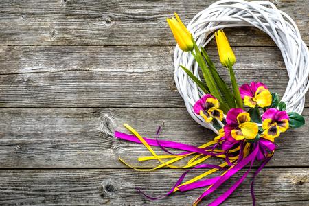 春の花がドアに花輪を持つイースターの背景
