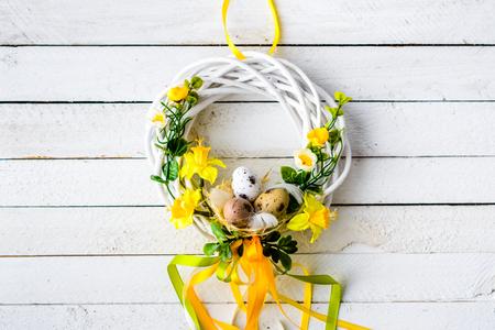 Pasen-achtergrond met de lentepaaseieren en bloemen, kroon op deur