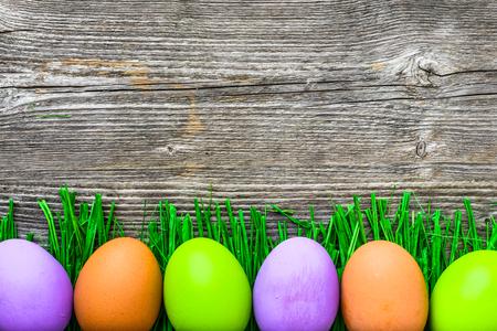 草に描かれた卵、幸せなイースターエッグの背景 写真素材