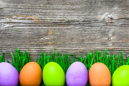 Painted eggs on grass, happy easter eggs background