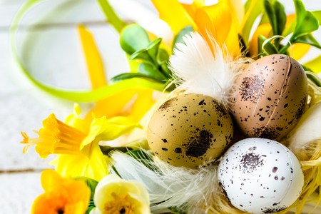 Easter background with spring easter eggs and flowers on wooden table