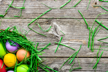 Basket with easter eggs, background with colorful eggs, spring festive decoration on wooden background
