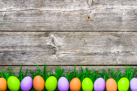 Wooden background with easter eggs painted in vibrant colors Stock Photo