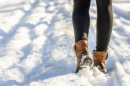 Female feet in boots and leggings, winter walking in snow