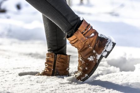Women's boots in snow, brown shoes for winter Stock Photo