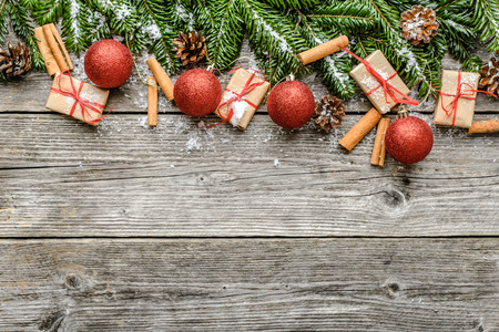 Fir branches with decorations - gift boxes, pine cones, holly and red ornements. Christmas background, top view, copy space. Imagens
