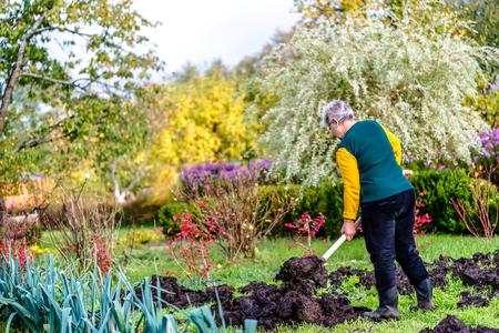 Gardener working in the garden or farmer fertilizing the soil with a natural fertilizer, organic farming concept