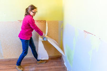Home renovation, room wall repairing, woman removing old wallpaper Imagens
