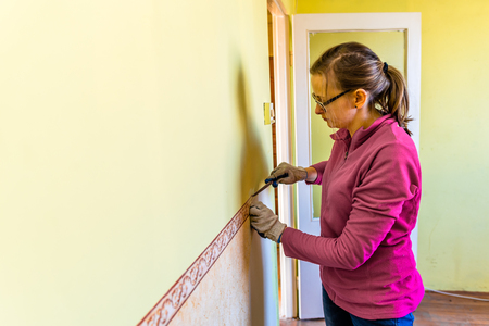 Woman Removing Old Wallpaper From The Wall Home Renovation Concept