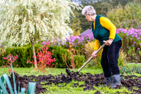 Working farmer in the autumn garden. Organic fertilizer for manuring soil, preparing field for planting in spring, bio farming concept. Stok Fotoğraf - 97366775