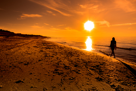 Sunset beach. Woman walking over sea in the sun, summer background, Baltic Sea, Poland Banco de Imagens
