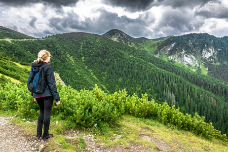 Woman hiker with backpack hiking in the mountains, travel lifestyle and active vacations in outdoors Stock Photo