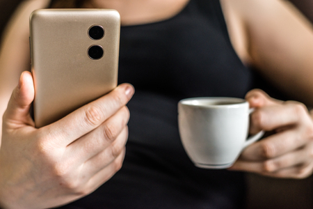 Person with mobile phone in hand, back view of smartphone with dual camera Stock Photo