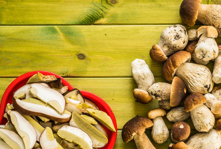 Boletus mushrooms, fresh, whole and sliced on wooden table.