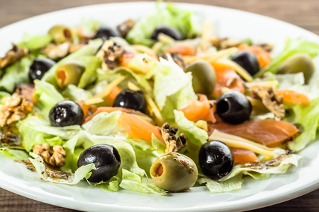 Mediterranean salad with vegetables, lettuce, salmon and olives, healthy diet concept