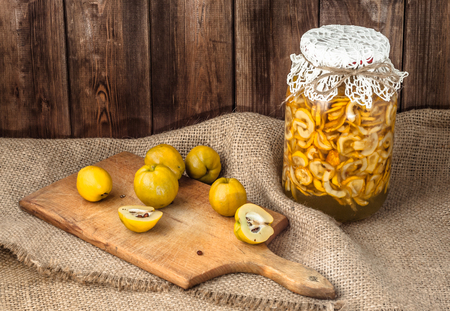 木製のテーブルの上のアルコールチンキと新鮮なクインスフルーツの瓶