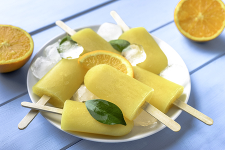 Orange  on blue wooden background. Summer refreshing ices on stick.