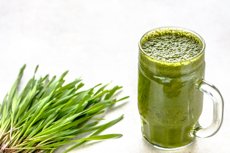 Healthy detox drink with green barley grass, organic juice in jar on white background