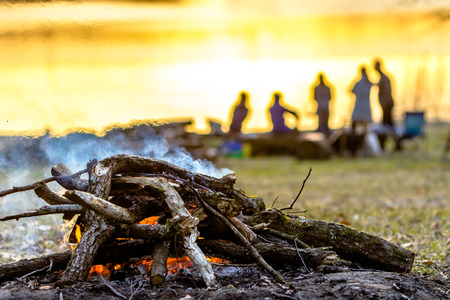 Family campfire, people on camp in the summer over sunset lake Banque d'images - 99403868