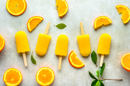Orange popsicles with juice. Ice pops, flat lay, top view