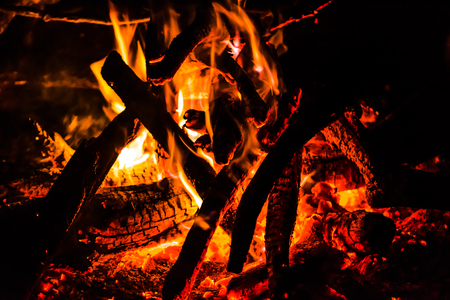 Night bonfire. Burning wood, flames and heat of fire on black background. 写真素材