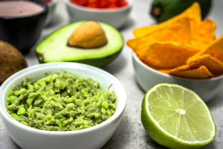 Traditional mexican sauce - guacamole dip with avocado and tortilla chips snack on table, party food for sharing Stok Fotoğraf