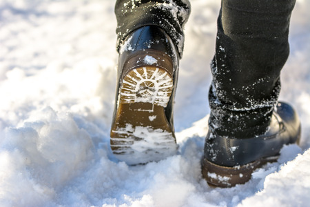 Fashionable male boots in snow, feet in the black shoes hiking in winter Archivio Fotografico - 99832862