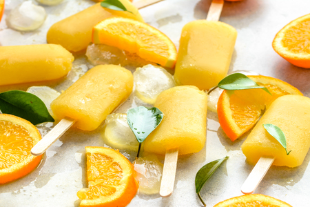 Orange  popsicles with frozen juice and ice cubes, summer refreshing snack Фото со стока